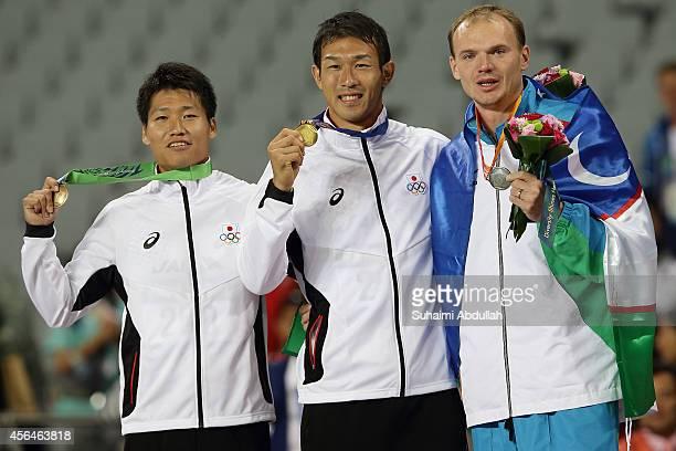 October 01: Bronze medallist Akihiko Nakamura of Japan, gold medallist Keisuke Ushiro of Japan and silver medallist Leonid Andreev of Uzbekistan pose...
