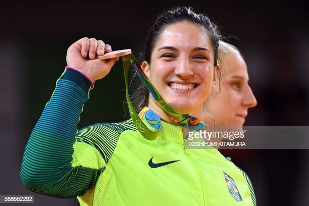 Bronze medallist Brazil's Mayra Aguiar celebrates on the podium of the women's 78kg judo contest of the Rio 2016 Olympic Games in Rio de Janeiro on...
