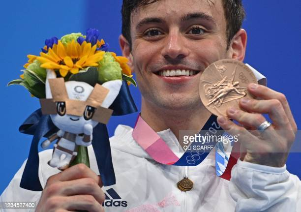 Bronze medallist Britain's Thomas Daley poses with their medal during the medal presentation ceremony after the men's 10m platform diving final event...