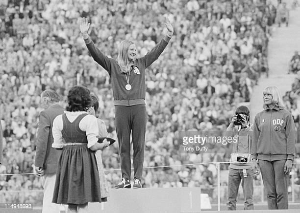 Bronze medallist Burglinde Pollak of East Germany looks up as Mary Peters of Great Britain raises her arms in triumph after receiving her gold medal...