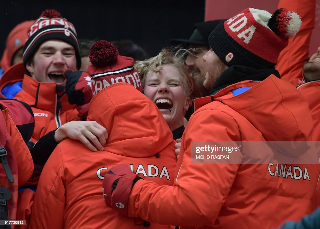 TOPSHOT - Bronze medallist Canada's Alex Gough (C) celebrates after the women's luge singles during the Pyeongchang 2018 Winter Olympic Games, at the Olympic Sliding Centre on February 13, 2018 in Pyeongchang. /