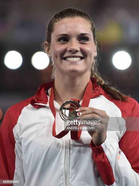 Bronze medallist Canada's Alysha Newman poses on the podium during the award ceremony for the women's pole vault athletics event at Hampden Park...