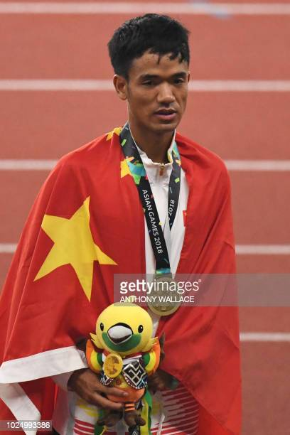 Bronze medallist China's Jin Xiangqian attends the victory ceremony for the men's 20km race walk athletics event during the 2018 Asian Games in...