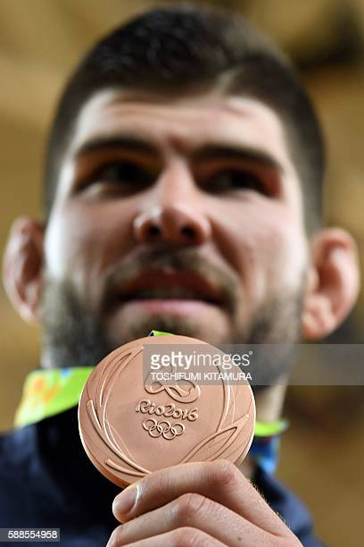 Bronze medallist France's Cyrille Maret celebrates on the podium of the men's 100kg judo contest of the Rio 2016 Olympic Games in Rio de Janeiro on...