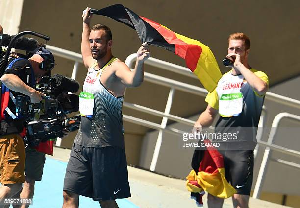 Bronze medallist Germany's Daniel Jasinski waves the German flag next to gold medallist Germany's Christoph Harting after the Men's Discus Throw...