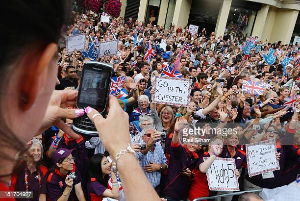 Bronze medallist gymnast Beth Tweddle of Great Britain takes a picture of the crowd as she takes part in the London 2012 Victory Parade for Team GB...