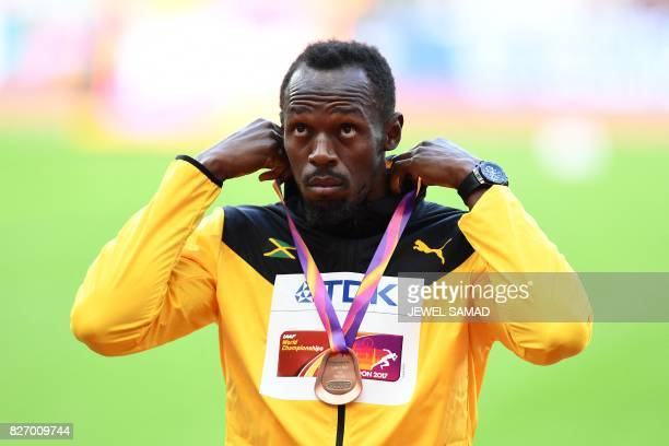 Bronze medallist Jamaica's Usain Bolt poses on the podium during the victory ceremony for the men's 100m athletics event at the 2017 IAAF World...