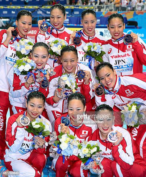 Bronze medallist Japan team poses for photographs with their medals after the medal ceremony for the Women's Free Combination Synchronised Swimming...
