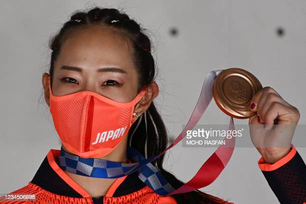 Bronze medallist Japan's Akiyo Noguchi celebrates on the podium during the women's sport climbing medal ceremony in the Tokyo 2020 Olympic Games at...