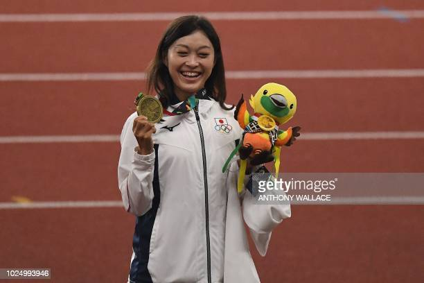 Bronze medallist Japan's Kumiko Okada celebrates during the victory ceremony for the women's 20km race walk athletics event during the 2018 Asian...