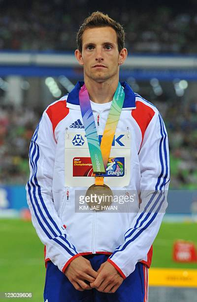 Bronze medallist Renaud Lavillenie of France stands on the podium during the award ceremony for the men's pole vault at the International Association...