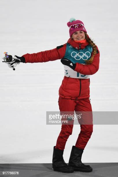 Bronze medallist Russia's Yulia Belorukova dances on the podium during the victory ceremony in the women's crosscountry individual sprint classic...