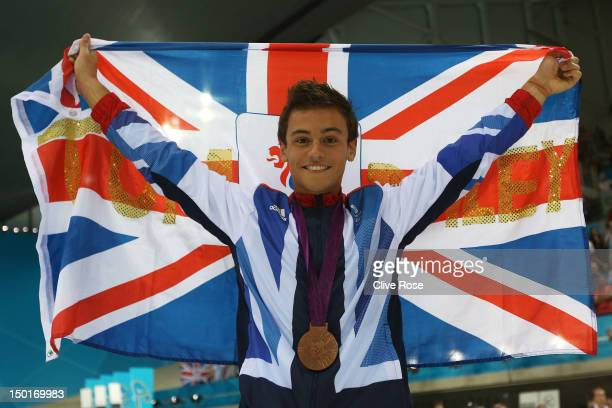 Bronze medallist Tom Daley of Great Britain poses with the national flag after the medal ceremony for the Men's 10m Platform Diving Semifinal on Day...