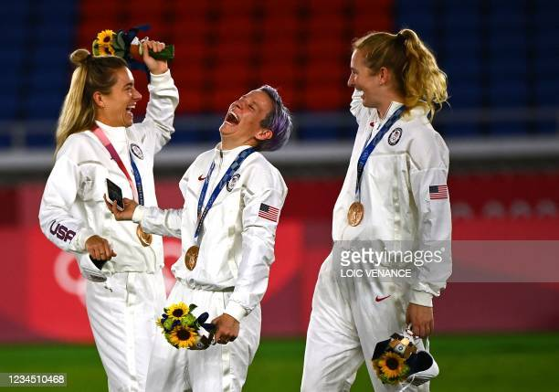 Bronze medallist USA's forward Megan Rapinoe smiles during the victory ceremony after the Tokyo 2020 Olympic Games women's final football match at...