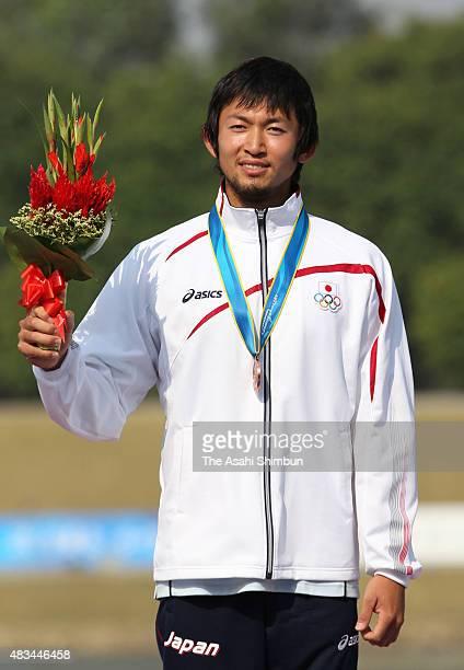 Bronze medallist Yasuhiro Suzuki of Japan celebrates on the podium at the medal ceremony for the Canoe Sprint Men's Kayak Single 1000m during day...