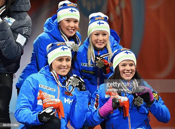Bronze medallists AinoKaisa Saarinen Kerttu Niskanen RiittaLiisa Roponen and Krista Parmakoski of Finland celebrate during the medal ceremony for the...