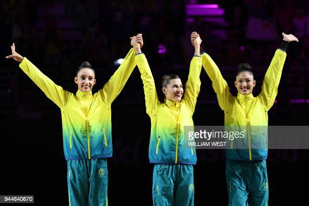Bronze medallists Australia's Alexandra KiroiBogatyreva Danielle Prince and Enid Sung celebrate on the podium after the rhythmic gymnastics team...