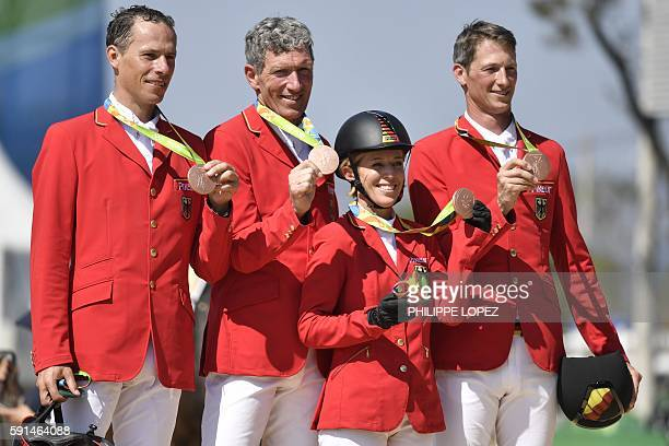 Bronze medallists Germany's Christian Ahlmann Ludger Beerbaum Daniel Deusser Merdith MichaelsBeerbaum pose during the podium ceremony of the jumping...