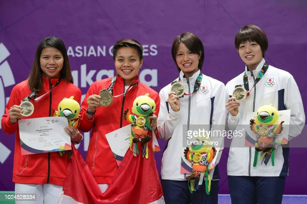 Bronze medallists Indonesia's Greysia Polii and Apriyani Rahayu and Yuki Fukushima and Sayaka Hirota of Japan celebrate during the victory ceremony...