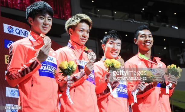 Bronze medallists Japan's Shuhei Tada, Kirara Shiraishi, Yoshihide Kiryu and Abdul Hakim Sani Brown pose on the podium during the medal ceremony for...