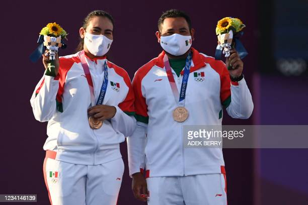 Bronze medallists Mexico's Alejandra Valencia and Luis Alvarez stand on the podium during the mixed team victory ceremony during the Tokyo 2020...