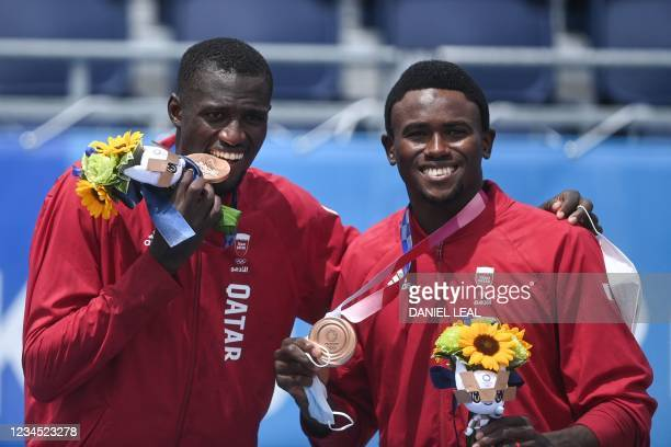 Bronze medallists Qatar's Cherif Younousse and Ahmed Tijan pose with their medals after the victory ceremony of the men's beach volleyball event...