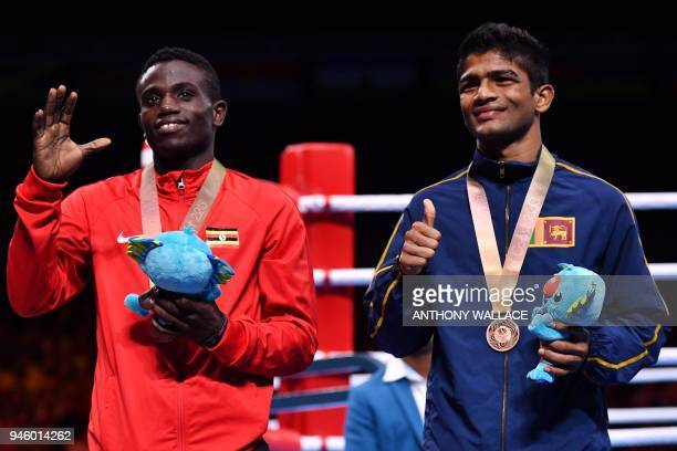 Bronze medallists Uganda's Juma Miiro and Sri Lanka's Thiwanka Ranasinghe pose with their medals during the medal ceremony for the men's 4649kg...