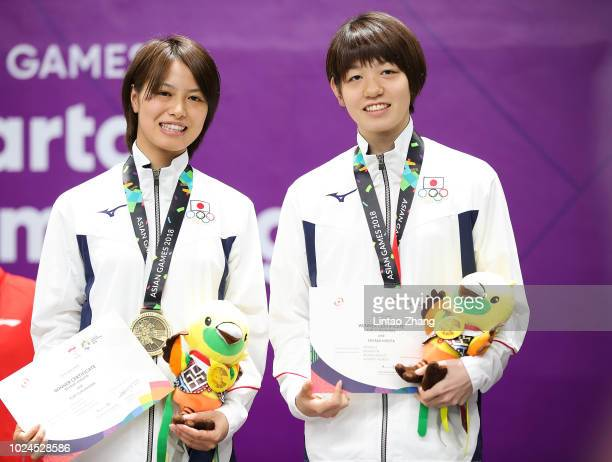 Bronze medallists Yuki Fukushima and Sayaka Hirota of Japan celebrate during the victory ceremony of the women's double badminton event on day nine...
