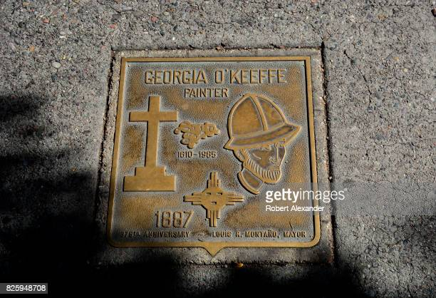 A bronze plaque embedded in the sidewalk in front of the New Mexico Museum of Art in Santa Fe New Mexico honors artist Georgie O'Keeffe a former...
