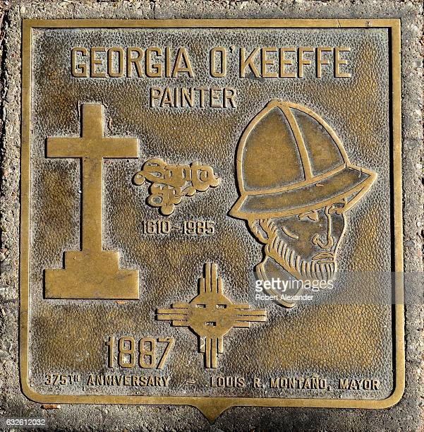 A bronze plaque honoring painter Georgia O'Keeffe is embedded in a sidewalk in front of the New Mexico Museum of Art in Santa Fe New Mexico After the...