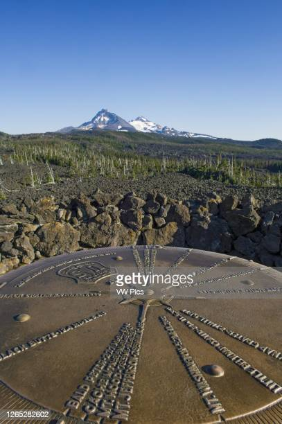Bronze plaque pointing out mountain peaks seen from Dee Wright Observatory at McKenzie Pass in the Cascade Mountains of Oregon, with North Sister and...