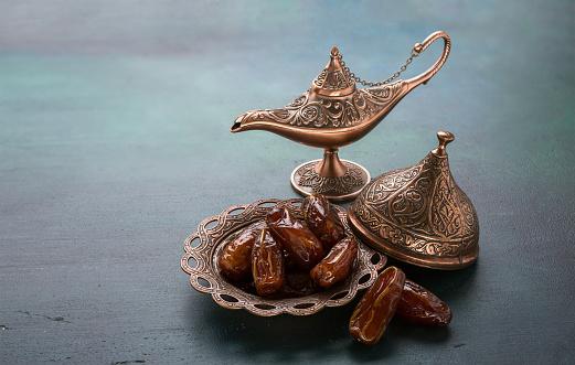 Bronze plate with dates  and aladdin lamp on dark green wooden background. Ramadan background. Ramadan kareem. 946208216