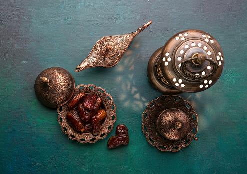 Bronze plate with dates, coffee cup, arabic lantern and aladdin lamp on dark green wooden background. Ramadan kareem.  Ramadan background.  Flat lay. 1068249006