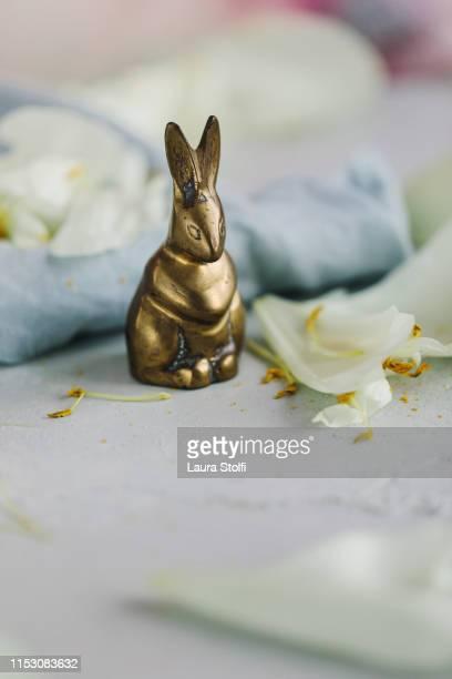 bronze rabbit miniature close to peony fallen petals and linen cloth - animali pasquali foto e immagini stock