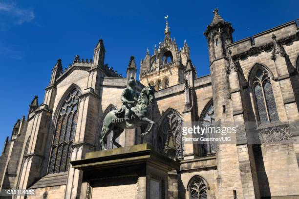 bronze sculpture of charles ii on horseback at south side of st giles' cathedral with crown steeple edinburgh scotland united kingdom - st. giles cathedral stock pictures, royalty-free photos & images