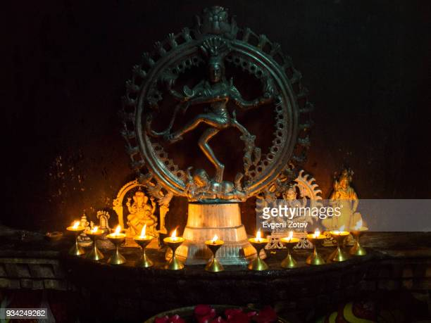 bronze sculpture of nataraja illuminated by little flaming lamps - shrine stock pictures, royalty-free photos & images
