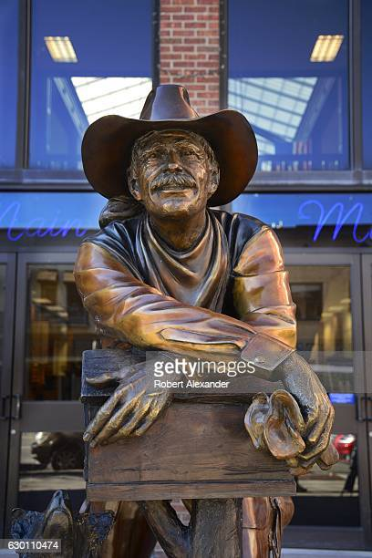 A bronze statue of a cowboy by George Lundeen stands in front of a shop in Durango Colorado