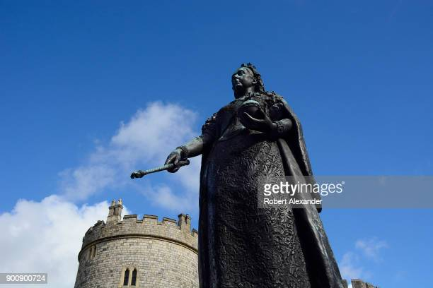 A bronze statue of Queen Victoria stands in front of the Curfew Tower at Windsor Castle in Windsor England The statue unveiled in 1887 was made by...