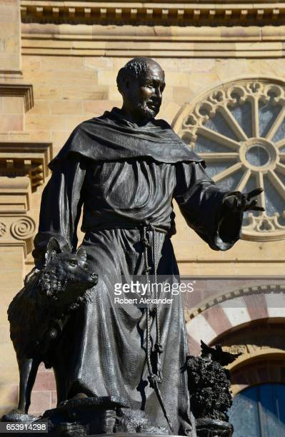 A bronze statue of Saint Francis of Assisi stands in front of the Cathedral Basilica of Saint Francis of Assisi in downtown Santa Fe New Mexico The...
