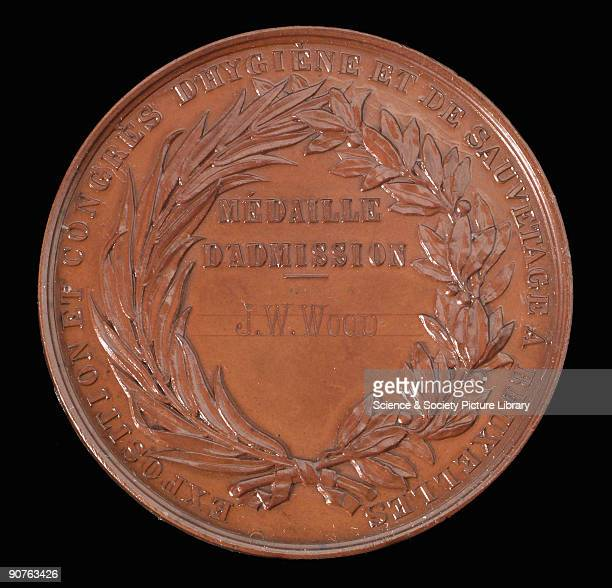 Bronze ticket medal issued to J W Wood for admission to and in commemoration of the Exposition et Congres d'Hygiene et de Sauvetage The design shows...