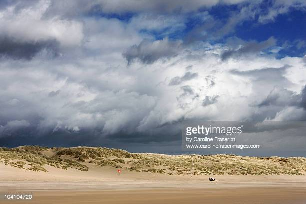 brooding cumulus clouds over camber - camber sands stock photos and pictures