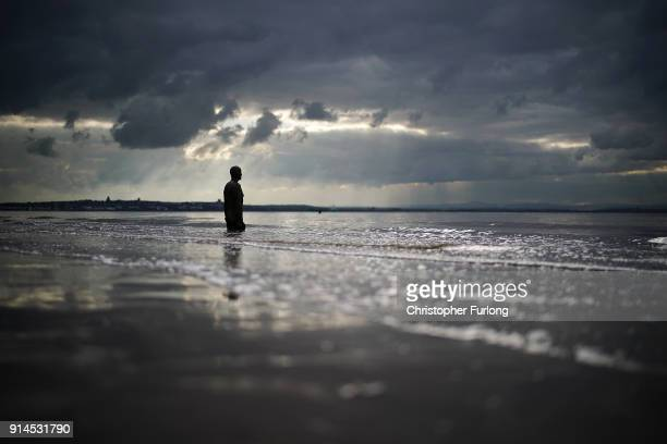 A brooding sky looms over a statue at Antony Gormley's art installation 'Another Place' at Crosby Beach on February 5 2018 in Liverpool England
