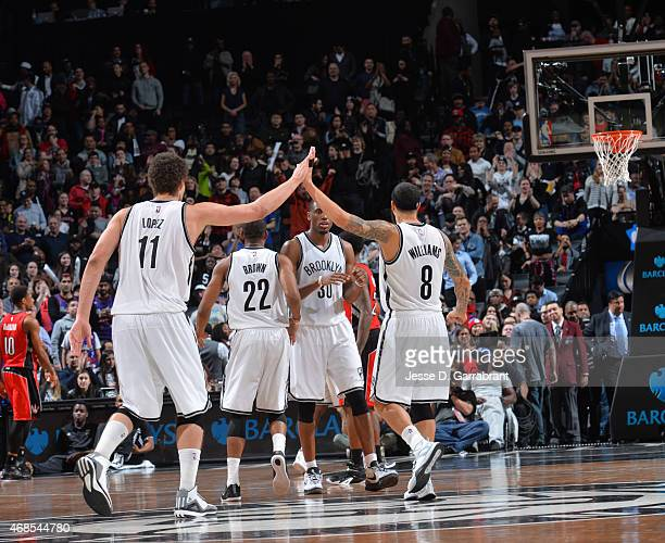Brook Lopez and Deron Williams of the Brooklyn Nets give each other high fives after the WIN against the Toronto Raptors at Barclays Center on April...