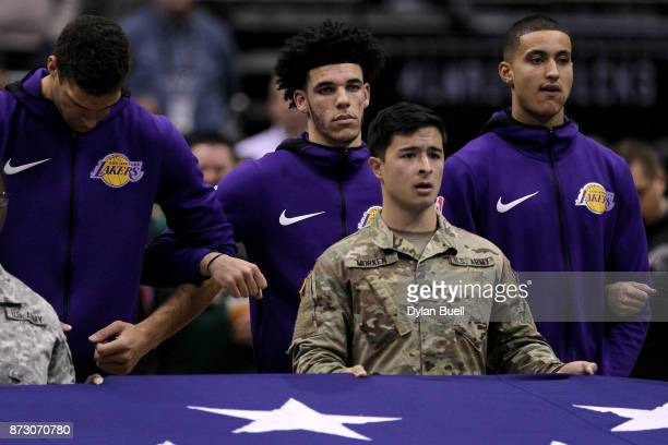 Brook Lopez Lonzo Ball and Kyle Kuzma of the Los Angeles Lakers look on during the singing of the national anthem before the game against the...