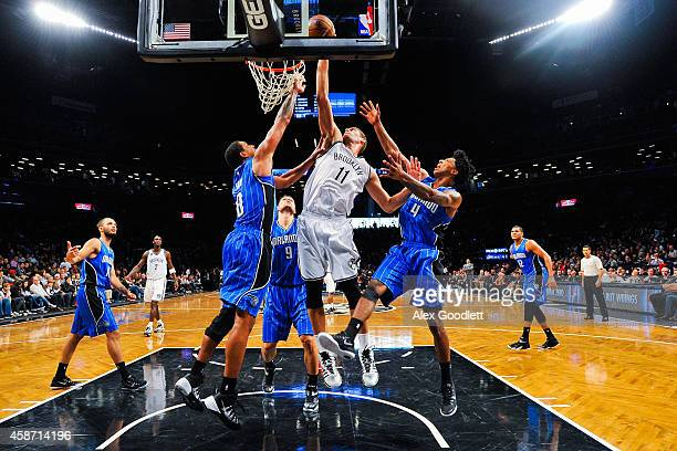 Brook Lopez of the Brooklyn Nets attempts a shot over Channing Frye and Elfrid Payton of the Orlando Magic in the second half at the Barclays Center...
