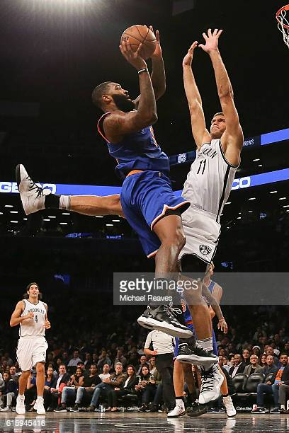 Brook Lopez of the Brooklyn Nets defends a shot by Kyle O'Quinn of the New York Knicks during the second half of their preseason game at Barclays...