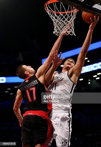 Brook Lopez of the Brooklyn Nets goes to the basket as Jonas Valanciunas of the Toronto Raptors defends at the Barclays Center on November 3 2012 in...