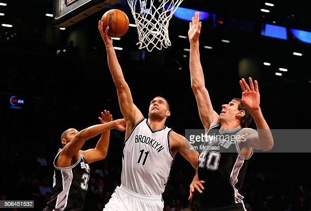 Brook Lopez of the Brooklyn Nets in action against Boban Marjanovic of the San Antonio Spurs at Barclays Center on January 11 2016 in the Brooklyn...