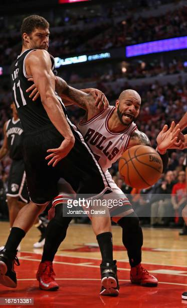 Brook Lopez of the Brooklyn Nets knocks the ball away from Carlos Boozer of the Chicago Bulls in Game Three of the Eastern Conference Quarterfinals...