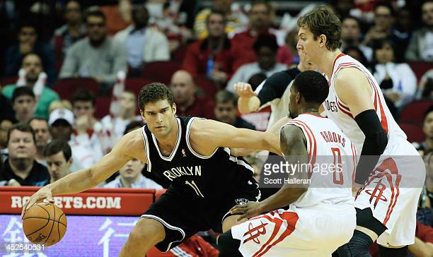Brook Lopez of the Brooklyn Nets works the ball against Aaron Brooks and Omer Asik of the Houston Rockets during the game at Toyota Center on...